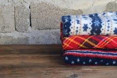 Bunt av varma woolen filtar på träbakgrund Hem- cosiness Färgrika pläd royaltyfria foton