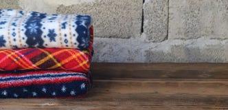 Bunt av varma woolen filtar p? tr?bakgrund Hem- cosiness F?rgrika pl?d royaltyfri bild