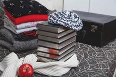 Bunt av vinterkläder och böcker med den glansiga kanten Fotografering för Bildbyråer