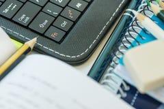 Bunt för blyertspenna för lärobok för bärbar datorminnestavla tangentbord öppnad av anteckningsbokpennan på vit skrivbords- dista fotografering för bildbyråer