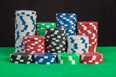 Bunt för pokerchiper på svartbakgrund för grön tabell Royaltyfri Fotografi