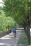 Bunt gekleidete Frau, die entlang den Fluss Mississipi in Minnesota geht lizenzfreies stockbild