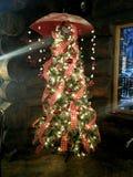 Bunt verzierter Weihnachtsbaum mit Regenschirm und Kette beleuchtet das Hängen von der Spitze Lizenzfreies Stockbild