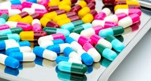 Bunt vom Antibiotikum kapselt Pillen mit Schatten auf Edelstahldrogenbehälter ein Lizenzfreie Stockfotos