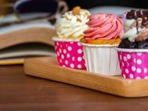 Bunt vom selbst gemachten kleinen Kuchen auf hölzernem Behälter auf und offenem Buch auf Holztisch Konzept des Lebensstils und en Lizenzfreie Stockbilder