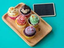 Bunt vom selbst gemachten kleinen Kuchen mit leerem Tafel- und Kopienraum für Ihren Text Kleiner Kuchen auf hölzernem Behälter au Lizenzfreie Stockfotografie
