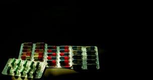 Bunt von den antibiotischen Kapselpillen in der Blisterpackung auf dunklem Hintergrund mit Kopienraum Medizin für Infektionskrank Lizenzfreies Stockfoto