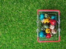 Bunt von multi Ostereiern im roten Warenkorb auf grünem Gras ist der Hintergrund hölzernes Brett Lizenzfreies Stockbild