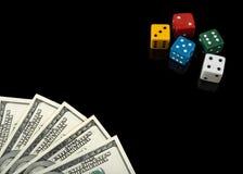 Bunt würfelt und Geld auf schwarzem Hintergrund Stockfotografie