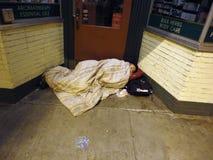 Buntad upp sömn för hemlös person i dörrväg av lagret under en bl arkivbilder