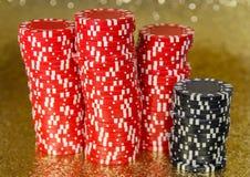 Buntar av den röda och svarta poker Chips Gleaming arkivfoton