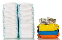 Buntar av disponibla, torkdukeblöjor och pengar som isoleras på vit Arkivbilder