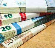 Buntar av euroräkningar på ett sörjaskrivbord Arkivfoton