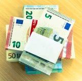 Buntar av euroräkningar på ett sörjaskrivbord med en tom etikett arkivfoto