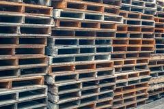 Buntar av gamla träpaletter i en industriell gård royaltyfri foto