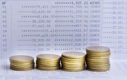Buntar av guld- mynt på bankrörelsekonto Arkivfoton
