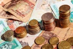 Buntar av mynt i form av tillväxtgraf äganderätt för home tangent för affärsidé som guld- ner skyen till Bakgrund med sedlar arkivfoto