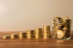 Buntar av mynt på en trätabell Det Glass kruset med myntar Affärsidé och tillväxt av huvudstad royaltyfri foto