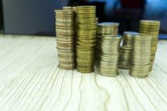 Buntar av mynt på olika höjder för vit bakgrund som förminskar inkomsten av affären arkivbilder