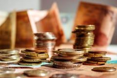 Buntar av mynt på sedlar coins sparande för stapel för begreppshandpengar skyddande framgång fotografering för bildbyråer