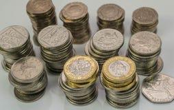 Buntar av olika brittiska mynt på en vit bakgrund Arkivbild