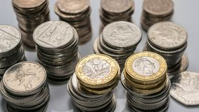 Buntar av olika brittiska mynt på en vit bakgrund Royaltyfri Bild
