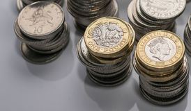 Buntar av olika brittiska mynt på en vit bakgrund Royaltyfri Foto