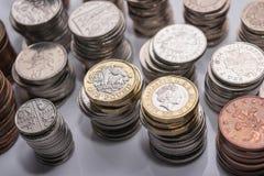 Buntar av olika brittiska mynt på en vit bakgrund Royaltyfria Foton