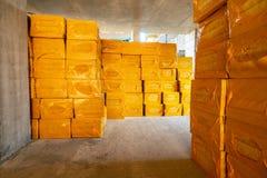 Buntar av packar med gul termisk isolering på konstruktionsplats av ny modern bostads- byggnad royaltyfri bild