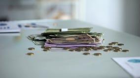 Buntar av sedlar och mynt på tabellen, utländsk valuta, lönförtjänster, kassa arkivfoton