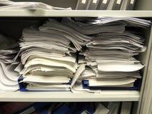 Buntar av skrivbordsarbete i flödande över skåp Arkivbilder