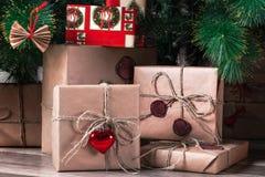 Buntar av slågna in julgåvor under trädet i en vardagsrum Arkivbilder