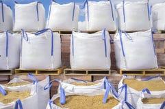 Buntar av stora sandsäckar för bast som staplas över träpalettwi arkivbild