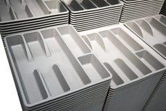 Buntar och rader av det gråa plast- bestickmagasinet Lätt att passa i sats arkivfoto