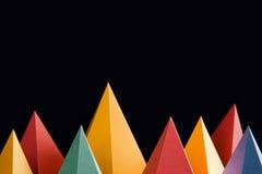 Bunte abstrakte geometrische Formen auf schwarzem Hintergrund Dreidimensionale Pyramide dreieckig Gelbes blaues rosa Malachit Stockfoto