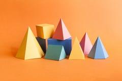 Bunte abstrakte geometrische Zusammensetzung Rechteckiger Würfel der dreidimensionalen Prismapyramide wendet auf orange Papier ei Lizenzfreies Stockbild