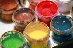 Bunte Acrylfarben in den kleinen Plastikdosen Stockfotos