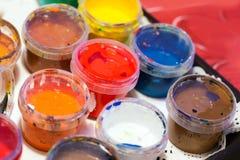 Bunte Acrylfarben in den Plastikdosen Lizenzfreies Stockfoto