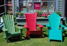 Bunte adirondack Stühle im Garten eines Systems Lizenzfreies Stockbild