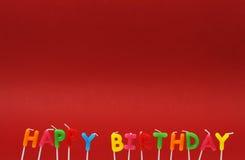 Bunte alles- Gute zum Geburtstagkerzen auf rotem Hintergrund Lizenzfreie Stockfotografie