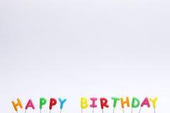 Bunte alles- Gute zum Geburtstagkerzen auf weißem Hintergrund Stockfotografie