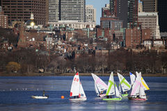 Bunte angekoppelte Segelboote und Boston-Skyline im Winter auf Halbgefrorenes Charles River, Massachusetts, USA Stockfotos