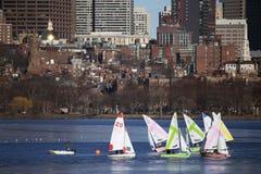 Bunte angekoppelte Segelboote und Boston-Skyline im Winter auf Halbgefrorenes Charles River, Massachusetts, USA Stockfotos