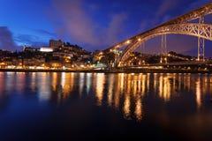 Bunte Ansicht des Sonnenuntergangs beim Ponte D. Luis Bridge mit den Leuchten, die im Duero-Fluss in Porto, Portugal sich reflekti Lizenzfreie Stockfotos