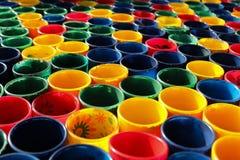 Bunte Aquarellfarbenbecher in einer Linie Stockfotos