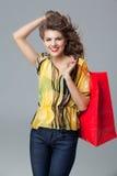 Bunte Ausstattung, die eine rote Einkaufstasche, smil anhält Stockfotografie