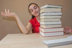 Bunte Bücher des gebundenen Buches auf Holztisch Junges Mädchen, das zu Hause am Schreibtisch, Hausarbeit tuend sitzt Lizenzfreie Stockfotografie