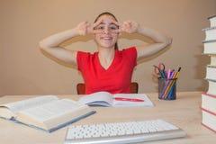 Bunte Bücher des gebundenen Buches auf Holztisch Junges Mädchen, das zu Hause am Schreibtisch, Hausarbeit tuend sitzt Stockfotografie