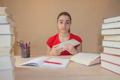 Bunte Bücher des gebundenen Buches auf Holztisch Junges Mädchen, das zu Hause am Schreibtisch, Hausarbeit tuend sitzt Stockfotos