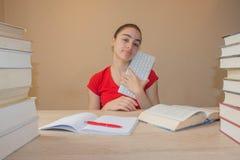 Bunte Bücher des gebundenen Buches auf Holztisch Junges Mädchen, das zu Hause am Schreibtisch, Hausarbeit tuend sitzt Lizenzfreie Stockfotos